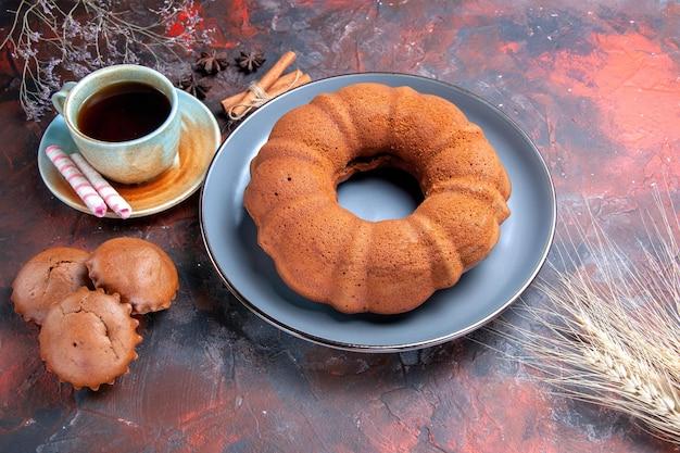 Zijaanzicht een taart een kopje zwarte thee een smakelijke taart cupcakes kaneel op de roodblauwe tafel