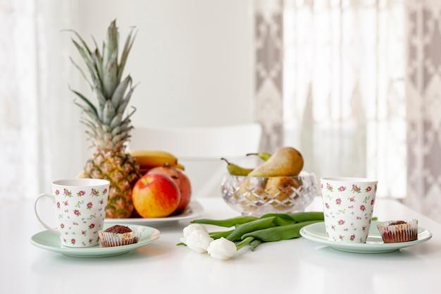 Zijaanzicht eenvoudig ontbijt met koffiemokken
