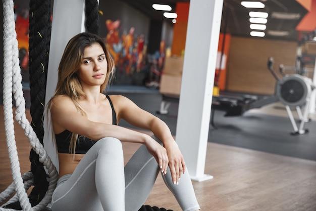 Zijaanzicht ernstig ogende atletische sterke sportvrouw, zittend in de buurt van hangende crossfit vechtende touwen.