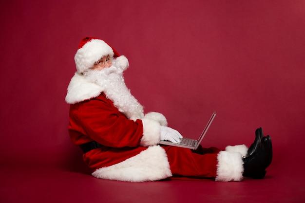 Zijaanzicht foto van gelukkig lachend kerstman gebruikt laptop