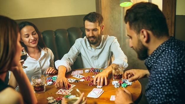 Zijaanzicht foto van mannelijke en vrouwelijke vrienden zitten aan houten tafel. mannen en vrouwen die kaartspel spelen. handen met alcoholclose-up. poker, avondentertainment en opwindingsconcept