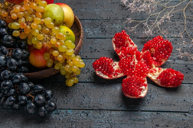 Zijaanzicht fruit in plaat bruin bord van witte en zwarte druiven limoenen peren appels naast gepilde granaatappel en takken op grijze achtergrond