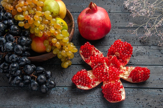 Zijaanzicht fruit in plaat bruin bord van witte en zwarte druiven limoenen peren appels naast gepilde granaatappel rijpe rode granaatappel en takken op grijze achtergrond