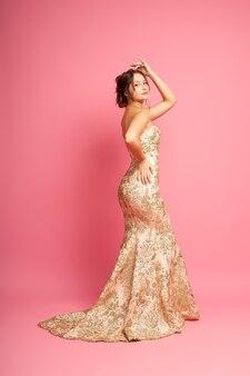 Zijaanzicht fulllength portret van aantrekkelijke vorstelijke vrouw in lange glanzende beige jurk met trein en l...