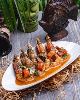Zijaanzicht gebakken garnalen in saus met tomaten en kruiden