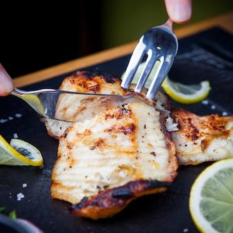Zijaanzicht gebakken vis met mes en vork