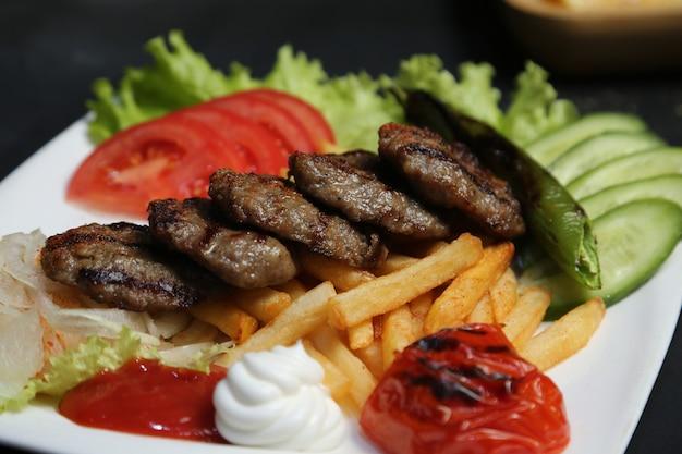 Zijaanzicht gebakken vlees kotelet met frietjes tomaten hete pepers komkommers en ketchup met mayonaise op een bord
