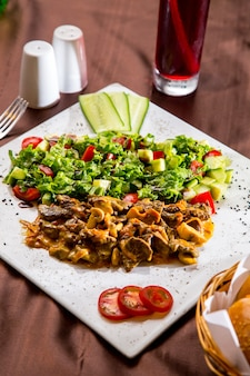 Zijaanzicht gebakken vlees met champignons in saus met groente salade en plakjes tomaat en komkommer