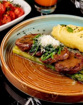 Zijaanzicht gebakken vlees op asperges met aardappelpuree en kruiden in een plaat