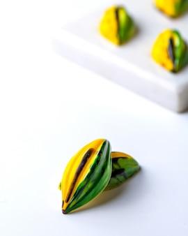 Zijaanzicht geelgroen in zwarte vlek chocoladesuikergoed op witte tribune