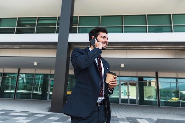 Zijaanzicht gelukkige advocaat die op de telefoon in openlucht spreekt