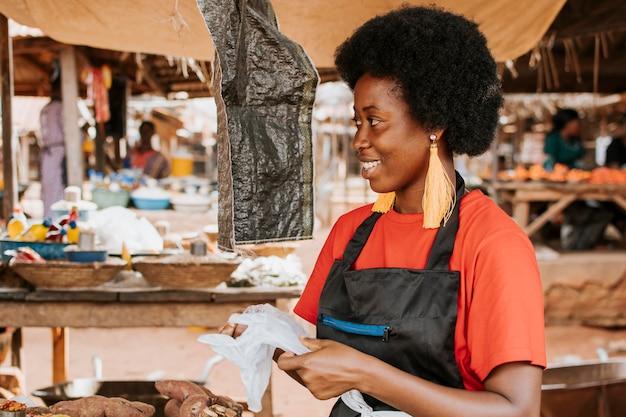 Zijaanzicht gelukkige afrikaanse vrouw op de markt