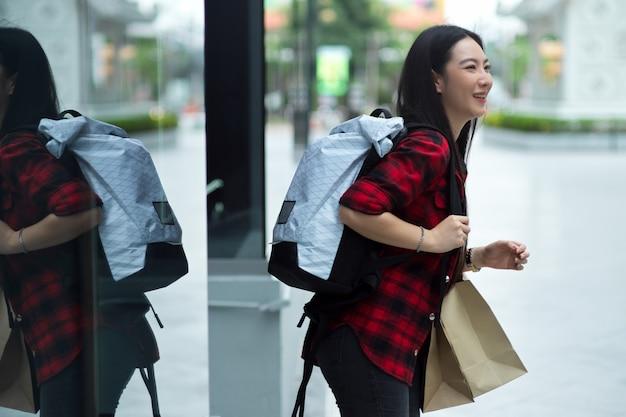 Zijaanzicht, gelukkige jonge vrouwelijke reiziger met zware rugzak en boodschappentassen die op straat in de stad lopen