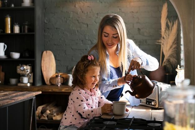 Zijaanzicht gelukkige moeder en dochter in de keuken