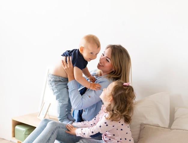 Zijaanzicht gelukkige moeder speelt met haar kinderen