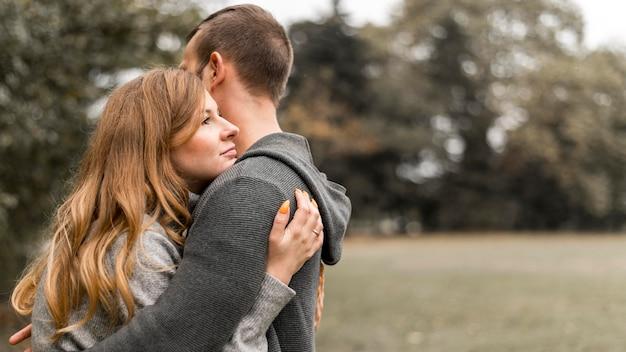 Zijaanzicht gelukkige partners knuffelen