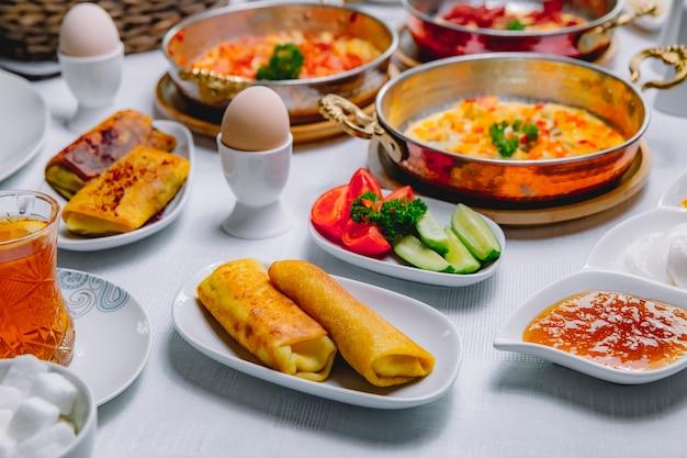 Zijaanzicht gerolde pannenkoeken met gekookte eieren, tomaten, komkommers en honing op tafel geserveerd ontbijt