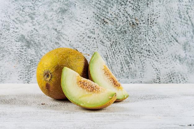 Zijaanzicht gesneden meloen met meloen op witte stenen achtergrond. horizontale kopie ruimte voor tekst