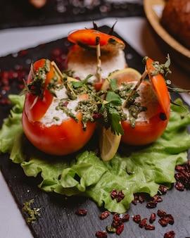 Zijaanzicht gevulde tomaten met saus op een blad van sla met gesneden citroen en gedroogde berberis