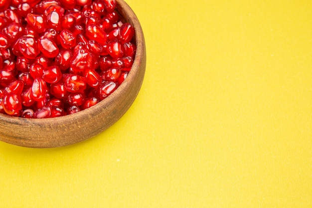 Zijaanzicht granaatappelpitjes van de smakelijke granaatappel in de bruine kom