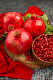 Zijaanzicht granaatappels zaden van granaatappel drie granaatappels met bladeren op de houten plank