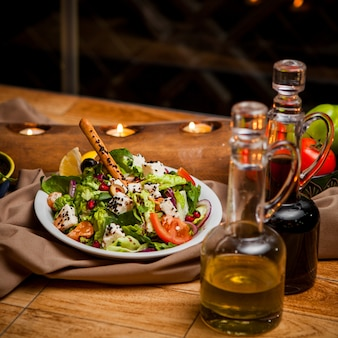 Zijaanzicht griekse salade met olijfolie en sojasaus en kaarsen in ronde witte plaat