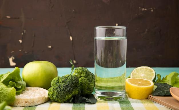 Zijaanzicht groene groenten en fruit appel brocoli sla knapperig knäckebröd glas water plak van citroen en limoen