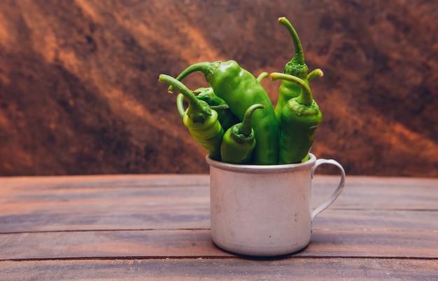 Zijaanzicht groene koreaanse paprika's in kop op houten lijst