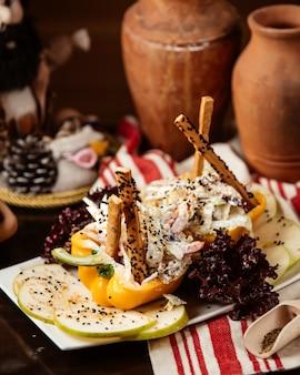 Zijaanzicht groentesalade met mayonaise in paprika met appelschijfjes en sesamzaadjes