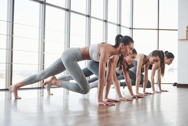 Zijaanzicht. groep sportieve meisjes in een ruime sportschool met grote ramen hebben training