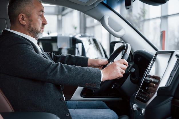 Zijaanzicht. hogere zakenman in officiële kleren die nieuwe luxeauto in autosalon proberen