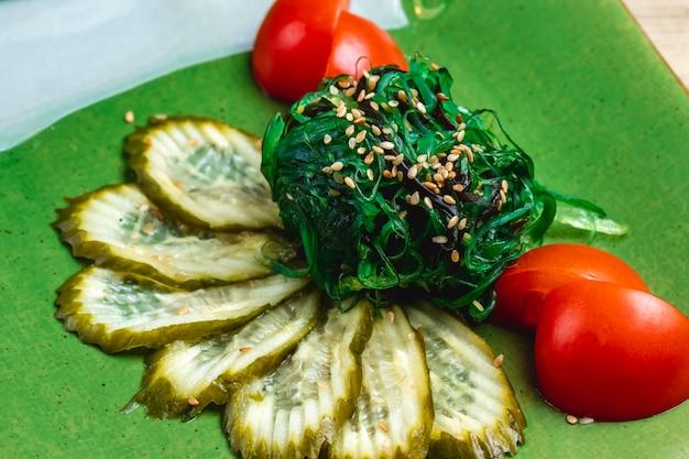 Zijaanzicht ingelegde komkommers zeewier en tomaat op tafel