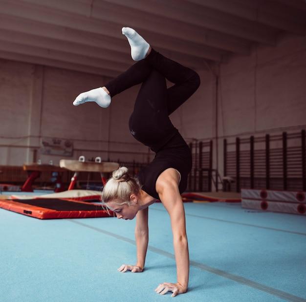 Zijaanzicht jonge blonde vrouw training voor gymnastiek kampioenschap