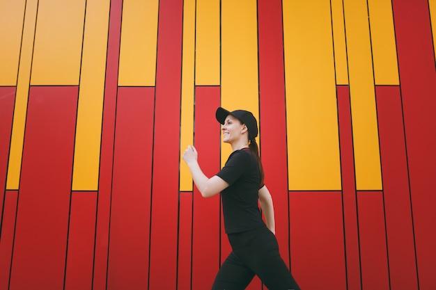 Zijaanzicht jonge lachende atletische mooie brunette vrouw in zwart uniform en pet wandelen zwaaiende handen voor of na de training buiten op lichte achtergrond