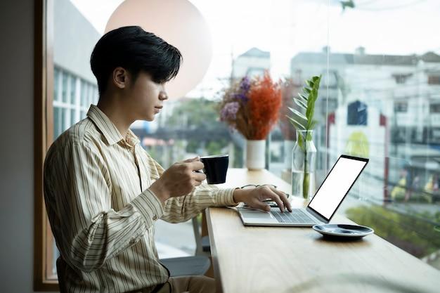 Zijaanzicht jonge man die koffie drinkt en computerlaptop gebruikt in een lichte kantoorruimte.