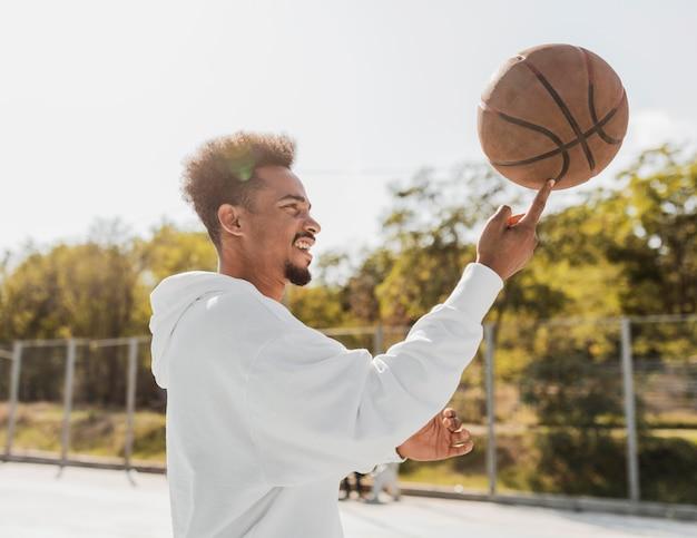 Zijaanzicht jonge man doet trucs met een basketbal