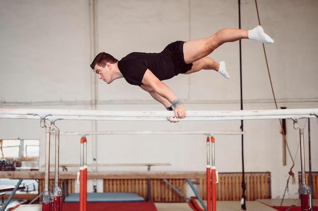 Zijaanzicht jonge man training op parallelle staven