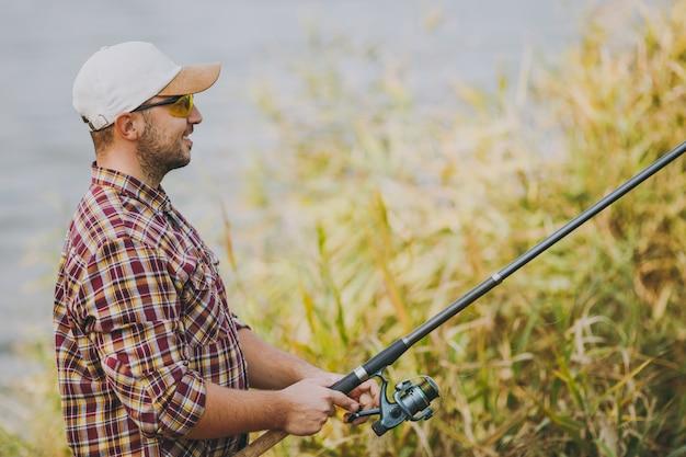 Zijaanzicht jonge ongeschoren glimlachende man in geruit hemd, pet en zonnebril houdt een hengel vast en wikkelt de haspel af aan de oever van het meer in de buurt van struiken en riet. lifestyle, vrijetijdsconcept voor vissers