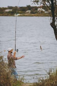Zijaanzicht jonge ongeschoren man in geruit hemd, pet en zonnebril trekt de hengel met gevangen vis op het meer van de kust in de buurt van struiken en riet. lifestyle, recreatie, vrijetijdsconcept voor vissers