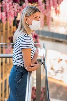 Zijaanzicht jonge vrouw die gezichtsmasker draagt