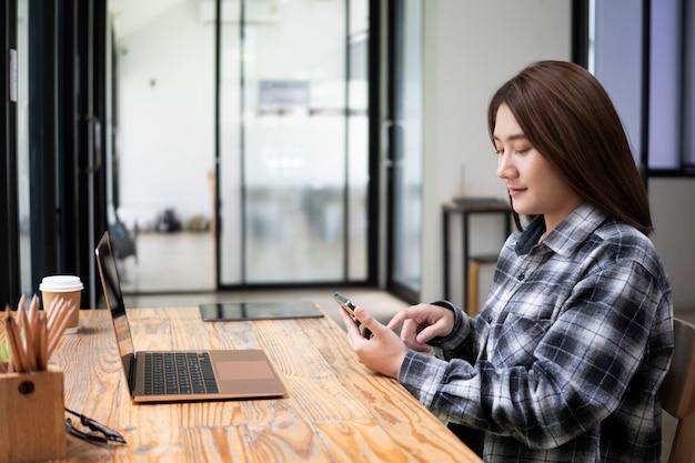 Zijaanzicht jonge vrouw die voor laptop op kantoor zit en mobiele telefoon gebruikt.