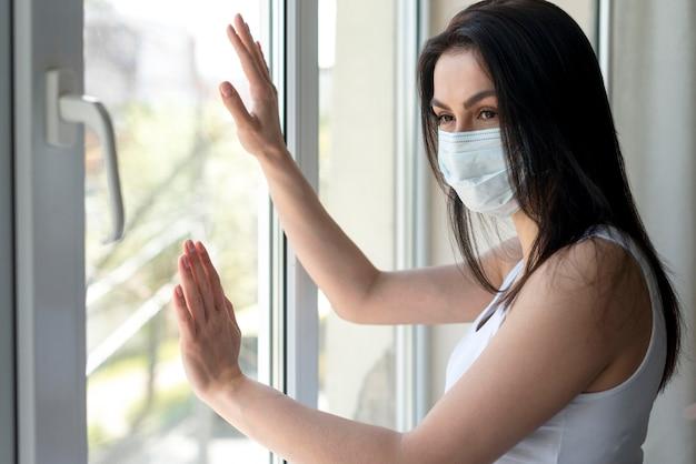 Zijaanzicht jonge vrouw met medisch masker