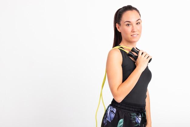 Zijaanzicht jonge vrouw met touwtjespringen