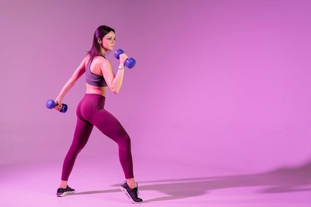 Zijaanzicht jonge vrouw training met gewichten