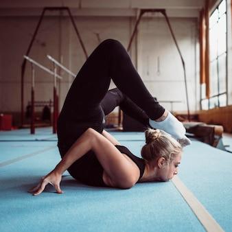 Zijaanzicht jonge vrouw training voor olympische gymnastiek