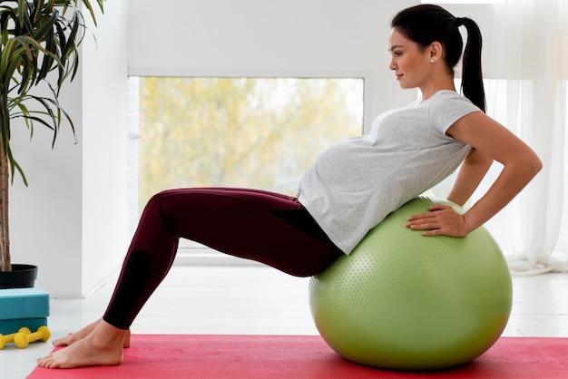 Zijaanzicht jonge zwangere vrouw die op geschiktheidsbal uitoefent
