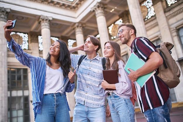 Zijaanzicht. jongeren maken overdag een selfie op straat