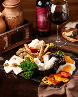 Zijaanzicht kaasplateau met druiven en een glas rode wijn
