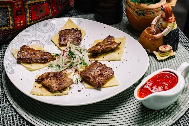 Zijaanzicht kalfsleverlever kebab op pitabroodje met uien en kruiden