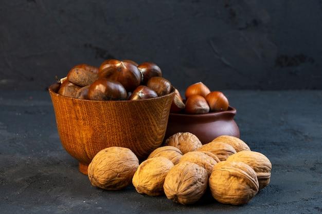 Zijaanzicht kastanjes in een beker met hazelnoten en walnoten